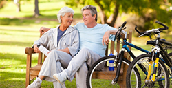 couple with bicycles sitting on a bench