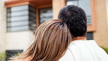 lady's head leaning on a man's shoulder while looking at a house