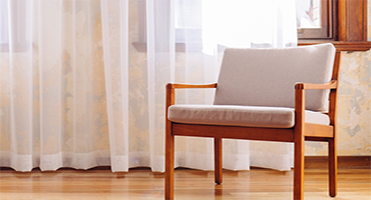 wooden chair in front of a white curtain
